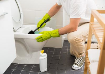 Man In Rubber Protective Gloves Cleaning And Washing Toilet With Brush And Bottle Of Cleaning Agent In Hands